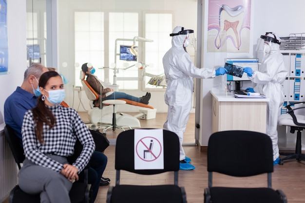 Stomatologie-tandarts gekleed in ppe-pak met röntgenfoto van de patiënt van receptioniste in de gang van de kliniek...