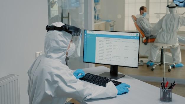 Stomatologie verpleegster zit aan bureau met behulp van moderne computer