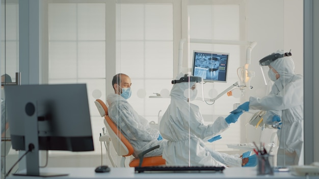 Stomatologieverpleegster die tandheelkundige röntgenfoto's geeft aan tandarts in kabinet