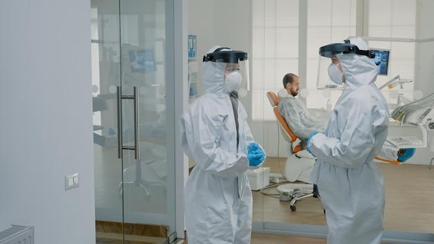 Stomatologische artsen die pbm-pakken dragen in de tandheelkundige kliniek