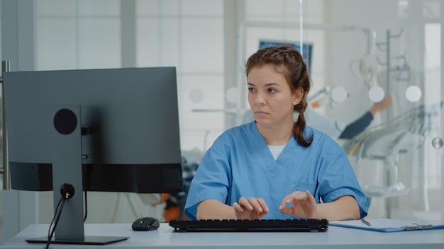Stomatologische assistent typen op computertoetsenbord