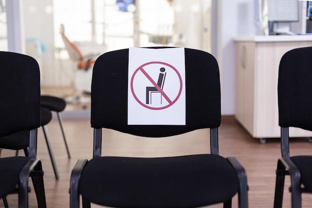 Stomatologische lege wachtkamer tijdens uitbraak van coronavirus met borden op stoelen met respect voor sociale afstand