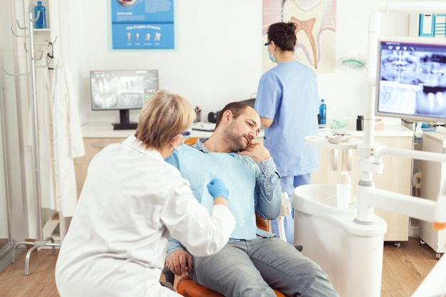 Stomatologist senior vrouw die patiënt tandpijn onderzoekt tijdens stomatologie consult stom