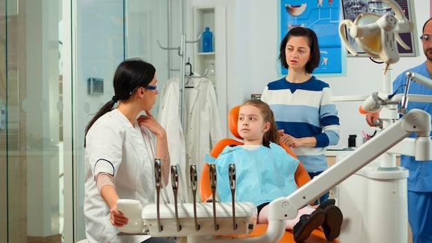 Stomatoloog arts die aan moeder het tandheelkundige proces van interventie voor tandproblemen van een kind uitlegt, meisje dat aan de aangetaste massa laat zien. orthodontist in gesprek met kind zittend op stomatologische stoel