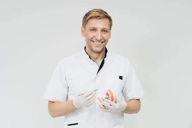 Stomatoloog arts die de juiste mondhygiëne uitlegt aan de patiënt die een monster van de menselijke kaak vasthoudt