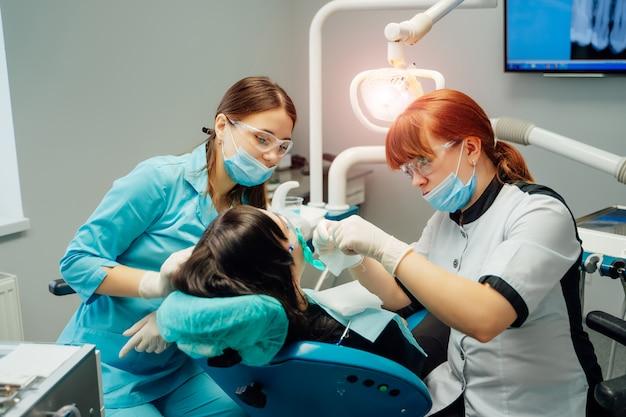 Stomatoloog en hulpvrouwen in maskers en beschermende glazen die met een vrouwelijke patiënt in tandartsbureau werken.