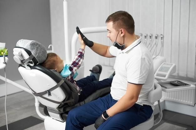 Stomatoloog en schattige jongen na het behandelen van tanden