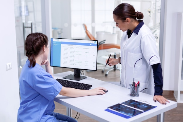 Stomatoloog en verpleegkundige in de tandkliniek die de afspraak van de patiënt controleren en naar de computermonitor kijken. stomatologie assistent en tanden arts bespreken bij de receptie van de tandartspraktijk