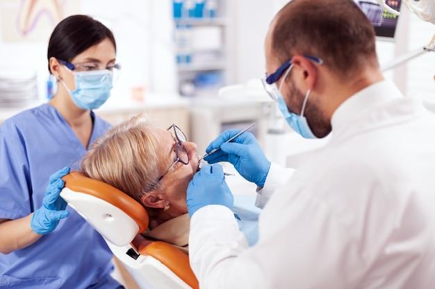 Stomatoloog en verpleegster behandelen tanden van senior vrouw met behulp van boor. oudere patiënt tijdens medisch onderzoek met tandarts in tandartspraktijk met oranje apparatuur.