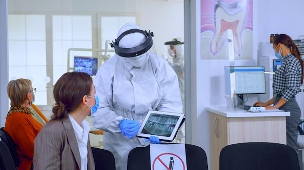 Stomatoloog in beschermend pak wijzend op digitale röntgenfoto van tand en uitleg aan patiëntbehandeling met tablet in covid-19 pandemie. medisch team dat gezichtsschild, overall, masker en handschoenen draagt.