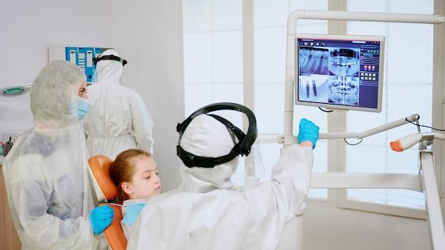 Stomatoloog in overall die tandheelkundig probleem uitlegt met behulp van digitale monitor tijdens wereldwijde pandemie. assistent en arts met overall gezichtsschild maskerhandschoenen die vrouw onderzoeken van stomatologische stoel