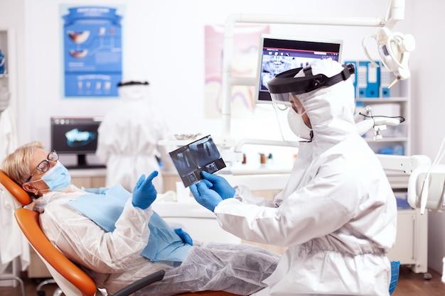 Stomatoloog in veiligheidsuitrusting tegen coronavirus met röntgenfoto van senior patiënt. oudere vrouw in beschermend uniform tijdens medisch onderzoek in tandheelkundige kliniek.