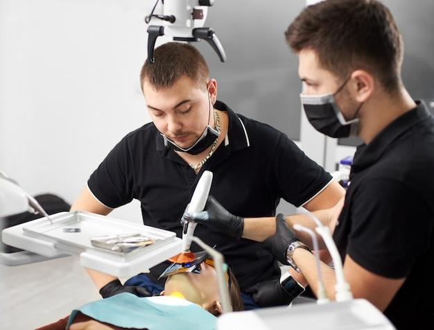 Stomatoloog kijkt naar de patiënt terwijl zijn assistent het proces van het vullen van de tand in de moderne kliniek voltooit. beide zijn gekleed in zwarte uniformen, maskers en handschoenen