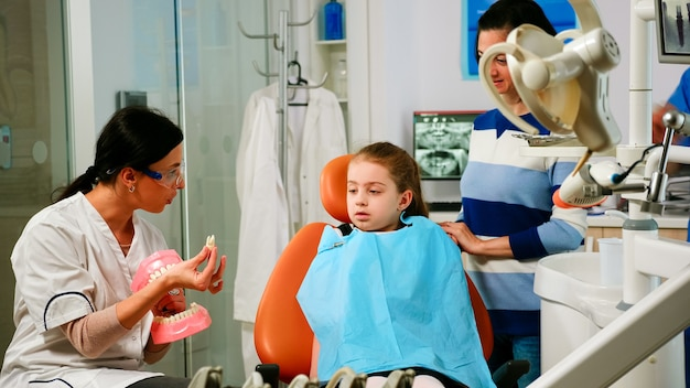 Stomatoloog legt aan het kind de operatie uit met behulp van een gipsmodel van de onderkaak die er een tand uit haalt. pediatrische tandarts met mock-up van skelet van tanden, monster van menselijke kaak praten.