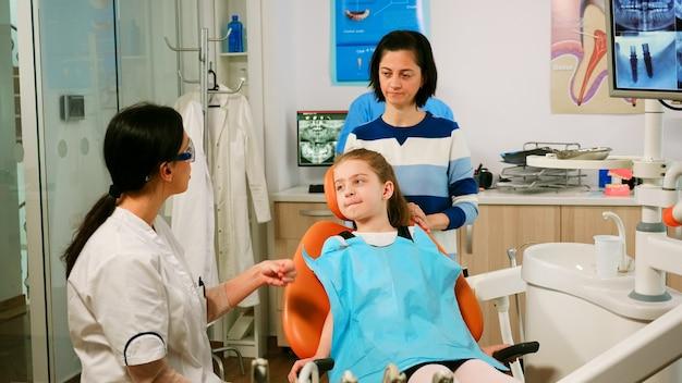 Stomatoloog legt aan klein meisje het reinigingsproces van tanden uit terwijl man-assistent gesteriliseerde hulpmiddelen voorbereidt voor onderzoek. verpleegkundige en arts werken samen in moderne stomatologische kliniek