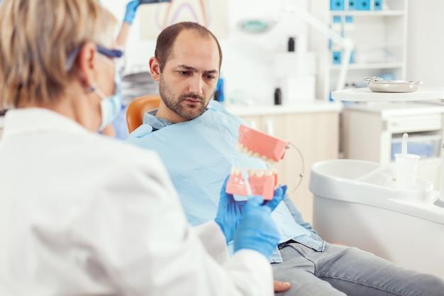 Stomatoloog legt goede mondhygiëne uit met behulp van tandenskelet tijdens afspraak voor stomatologie stom
