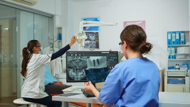 Stomatoloog-verpleegster die röntgenfoto's vergelijkt terwijl ze naar de computer kijkt, terwijl een gespecialiseerde arts met gezichtsmasker met een man spreekt met kiespijn die op een stomatologische stoel zit en hulpmiddelen voorbereidt voor een operatie