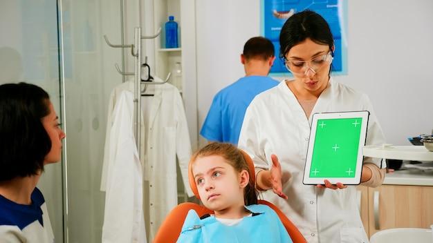 Stomatoloog-vrouw die naar een tablet met een groen scherm kijkt terwijl ze met de moeder van een kleine patiënt spreekt. pediatrische tandarts die uitlegt over het gebruik van een monitor met groene chroma key izolated chroma pc key mockup display