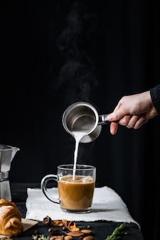 Stomen melk gieten in een kopje koffie. hete melk toevoegen aan espresso, gebrouwen in italiaanse mokka, rustig schot