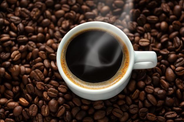Stomende espressokop op de achtergrond van koffiebonen. detailopname