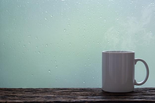 Stomende koffiekop op een achtergrond van het regenachtige dagvenster