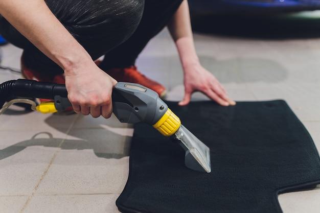 Stomerij van zwarte matten voor auto's, stofzuiger verwijdert vuil, roze rubberen handschoenen, autowassen.