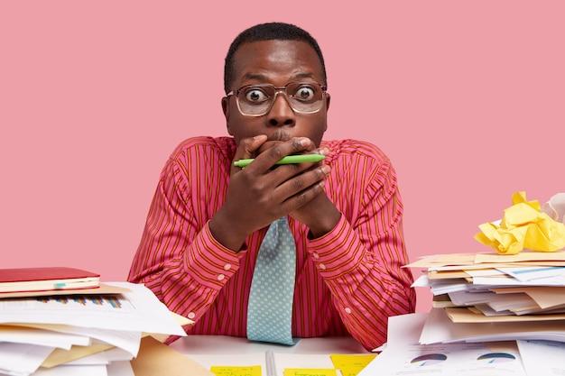 Stomme gruwelijke jonge man met donkere huid bedekt mond met handen, heeft ogen afgeluisterd, formeel gekleed, poseert op het bureaublad, omringd door veel papieren documenten
