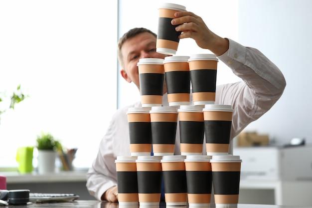 Stomme kantoorbediende die een enorme toren maakt van papieren bekertjes