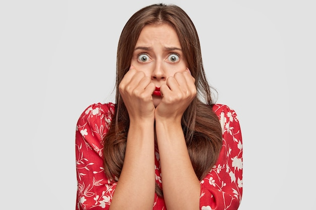 Stomverbaasde vrouw met rode lippenstift poseren tegen de witte muur