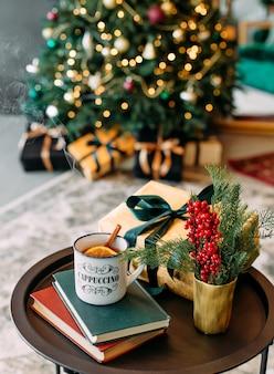 Stoom boven een kop hete thee met kerstdecor van citroen en kaneel en een elegante boom in bokeh