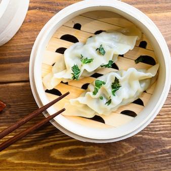 Stoom chinees eten van de dampende gyoza close-up op houten tafel