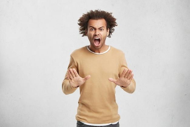 Stop alsjeblieft! geïrriteerde woedende man heeft afro kapsel maakt stop gebaar