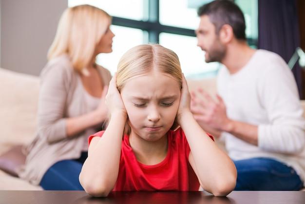 Stop alsjeblieft met vechten! depressief meisje leunt aan tafel en bedekt haar oor met handen terwijl haar ouders op de achtergrond tegen elkaar schreeuwen