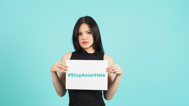 #stop aziatische haat schrijven in wit bordpapier. aziatische vrouw met papier op witte achtergrond.