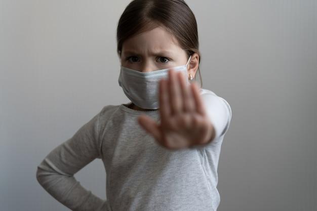 Stop coronavirus of covid 19 uitbraakconcept - jong meisje in medisch beschermend masker toont een stopgebaar met hand - meisje stak palm uit met angst, concept van quarantaine of thuisisolatie
