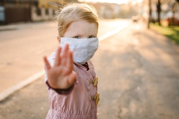Stop de coronavirus- en virusepidemische ziekten. gezond kind in medisch beschermend masker dat gebaareinde toont. bescherming en preventie van de gezondheid tijdens griep en besmettelijke uitbraak.