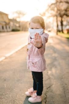 Stop de coronavirus- en virusepidemische ziekten. gezond kind in medisch beschermend masker dat gebaareinde toont. bescherming en preventie van de gezondheid tijdens griep en besmettelijke uitbraak