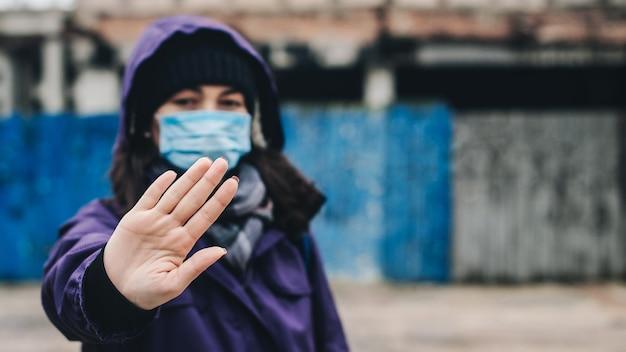 Stop de covid-vrouw die een veiligheidsmasker draagt bij het afsluiten van een straatcoronavirus-epidemie
