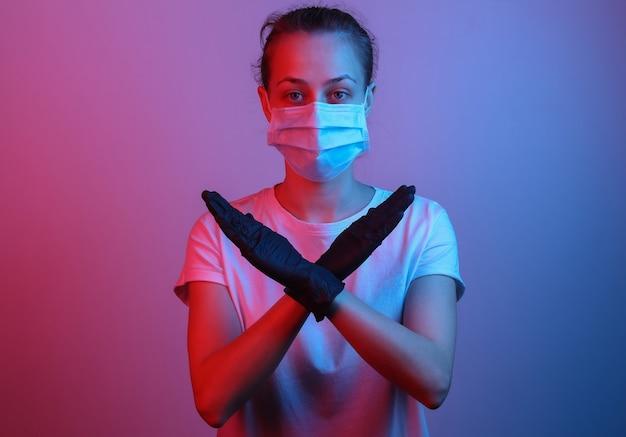 Stop de pandemie. vrouw met een gezichtsmasker houdt haar handen kruiselings vast. rood-blauw neonlicht