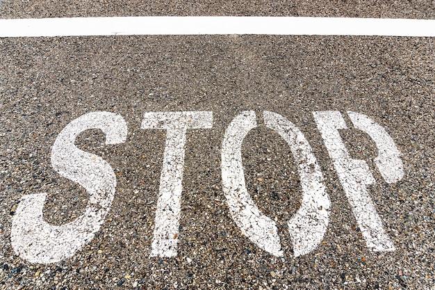 Stop een grote inscriptie op het asfalt