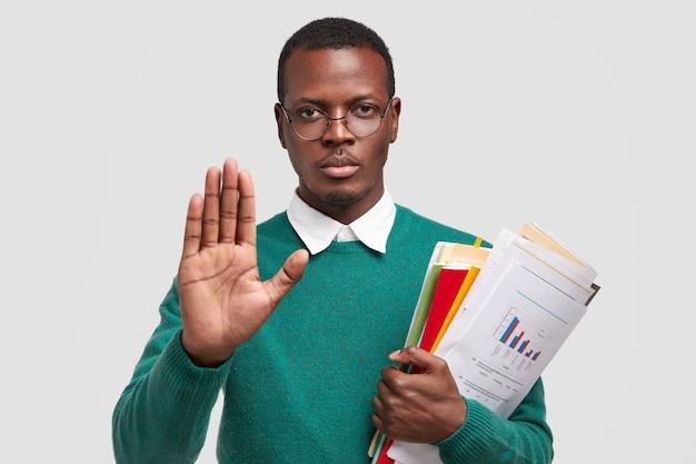 Stop ermee, alsjeblieft. ernstige zwarte man maakt weigeringsgebaar, draagt financiële documenten, vraagt hem niet lastig te vallen, draagt een bril
