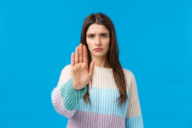 Stop ermee, genoeg. ontevreden serieus en beu jong assertief meisje, met stopgebaar, handpalm omhoog en fronsende afkeuring, weigeren, verbieden en niet mee eens, staand blauw