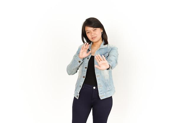 Stop handgebaar van mooie aziatische vrouw die jeansjasje en zwart overhemd draagt dat op wit wordt geïsoleerd