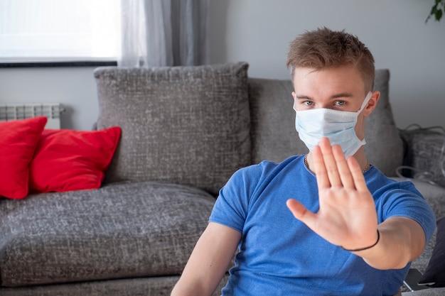 Stop het coronavirus-concept. man in medisch beschermend masker met gebaar stop. man thuis. quarantaine