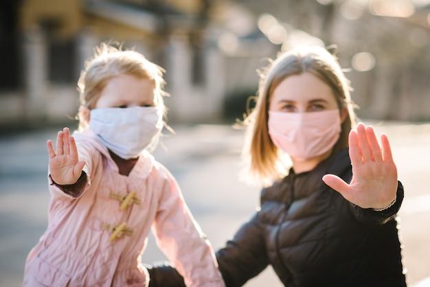 Stop het coronavirus en epidemische ziekten. gezonde vrouw en kind in medisch beschermend masker dat gebaareinde toont. bescherming en preventie van de gezondheid tijdens griep en besmettelijke uitbraak. Premium Foto