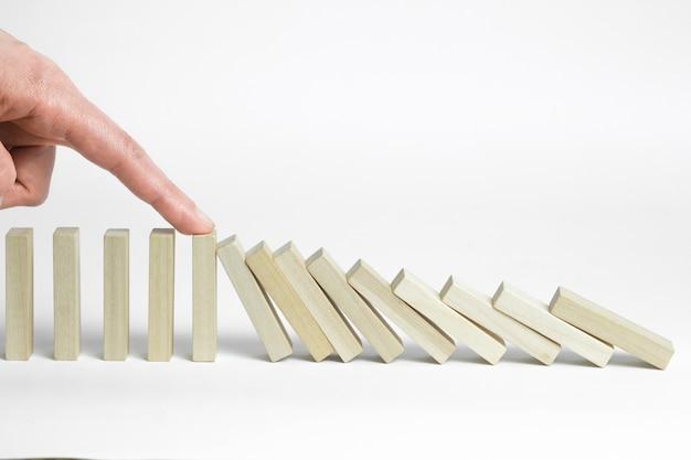 Stop het effect van het domino-effect. de vinger stopt de vallende houten blokken.
