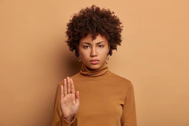 Stop hier. ernstige donkere vrouw staat met uitgestrekte hand, maakt verbodsgebaar, verbiedt iets, grijnst gezicht