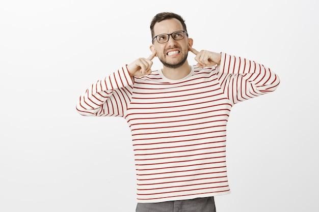 Stop met dit geluid. portret van geïrriteerde pissige blanke man in zwarte bril, oren bedekt met wijsvingers en grimassen van woede