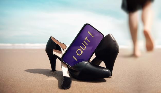 Stop met een baanconcept. zakenvrouw doet werkschoenen uit en laat deze op het zandstrand achter voor walk into the sea. ik stop met bericht op mobiele telefoon. zomervakantie. lage kijkhoek