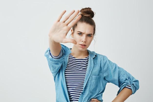Stop met het maken van foto's van mij. portret van geërgerde boze europese vrouw in modieuze kleding die hand naar camera trekt, proberend om zich van flits te bedekken, zeggend einde of genoeg